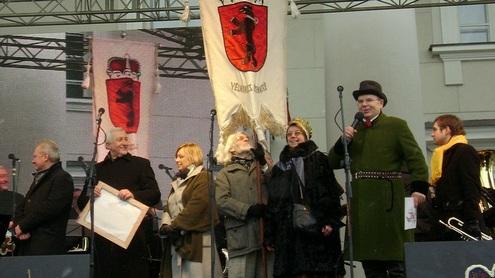 """Į sceną įnešta """"Vėlniaus žematės"""" vėliava. S. Kavaliauskas skelbia žemaičių vadovavimą Kaziuko mugei kitąmet. Autorės nuotr."""