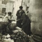 Vilnius apie 1930 m. Gatvės prekeivė. Žydų gatvės ir Ramailės skersgatvio kampas. Nuotraukos kairėje - Didžiosios sinagogos vartai. Šaltinis: Vilniaus miesto studija.