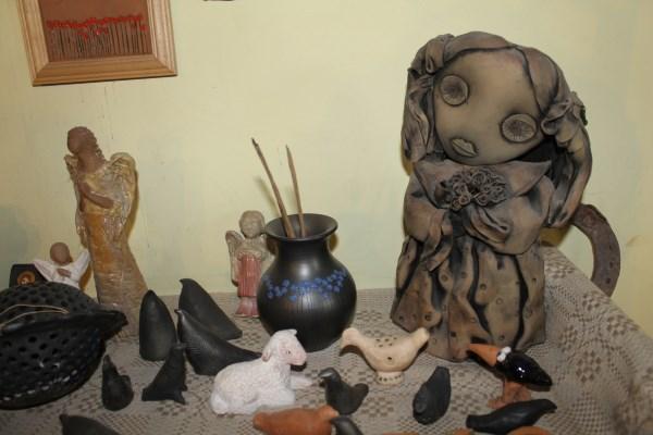 Dešinėje stovinti statulėlė lietuvaitė buvo laikoma tautodailininkės simboliu. Dauguma lėlių iš pirmosios personalinės parodos puikuojasi Mataičių dirbtuvėse. Autorės nuotr.