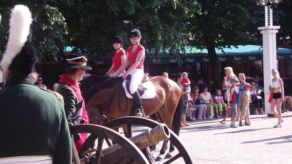 Alvija Gražulytė su žirgu lydi karietą Alytaus miesto centre.