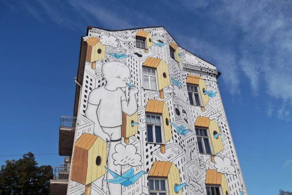 Didelio formato piešiniai ant pastatų sienų – tai Vilnius street art festival dalyvių darbai. Vienas jų – italų menininko Millo piešinys. Jį vis dar galite pamatyti priešais Halės turgų. Autorės nuotr.