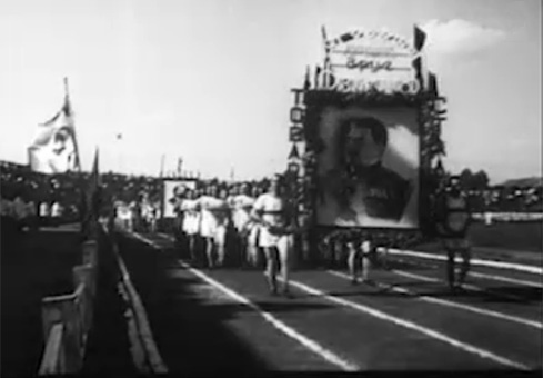 """Sportininkų kolona neša Stalino portretą. Epizodas iš 1946 m. dokumentinio filmo ,,Tarybų Lietuva"""""""