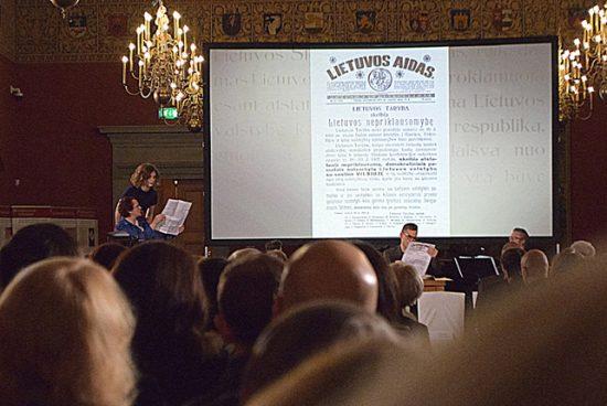 """Aktoriai V. Podolskaitė (sėdi kairėje, Vilniaus konferencijos ir Lietuvos Tarybos dokumentų perrašinėtoja 1928 metais), J. Nemanytė (stovi kairėje, šiuolaikinė doktorantūros studentė) ir D. Stončius (sėdi dešinėje, profesorius, doktorantės darbo vadovas) bando suprasti, koks iš tikrųjų buvo Lietuvos valstybės atkūrimo kelias. Aptarimo ir nuomonių sandūros centre – 1918-ųjų vasario 19-osios """"Lietuvos aido"""" numeris, skelbiąs atstatytą Lietuvos valstybę. Scenarijaus autorius – Andrius Vaišnys, režiserius – Vytenis Pauliukaitis. Autoriaus nuotr."""