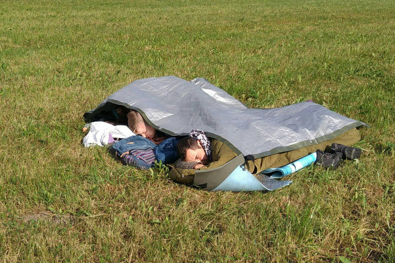 Skautai, pasikloję ir apsikloję tentu, kad nesušlaptų nuo lietaus, miegojo ant Apuolės piliakalnio 2017 m. Iš asmeninio M. M. Lizzi archyvo.
